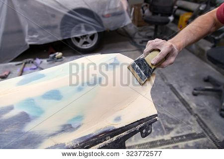 A man prepares a car body element for painting after an accident with the help of grinding abrasive paper in a car repair shop. Recovery bumper after a collision. stock photo