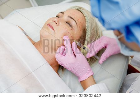 Beautician doing facial injection for woman. Anti-aging revitalization cosmetology procedure stock photo