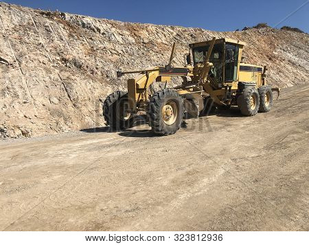 Planning of a road surface. Motor grader during road construction works. Earthmoving, excavations, digging stock photo