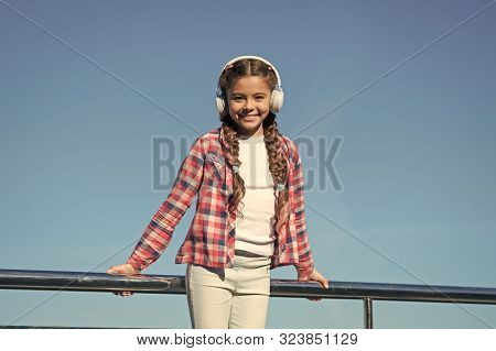 Make your kid happy with best rated kids headphones available right now. Girl child listen music outdoors with modern headphones. Enjoy sound. Kids headphones tested and ranked best to worst. stock photo