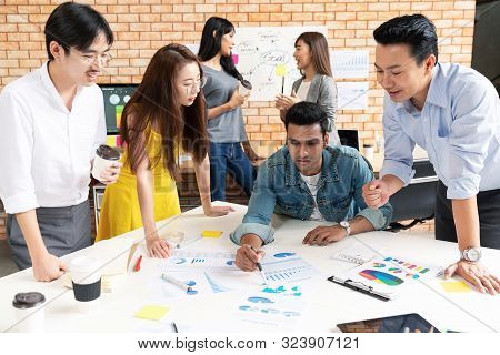 Asian group of business people teamwork meeting and working together. Creative design team brainstorming for strategy and business marketing plan. Group of friends or colleagues business meeting. stock photo