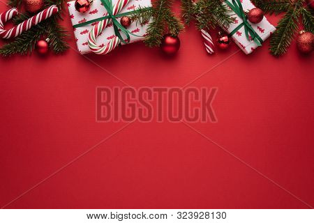 Red Christmas and New Year background. Decorative border of fir branches, gifts, Christmas balls and