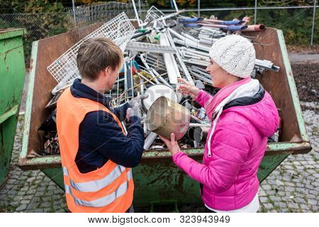 Woman putting lots of scrap metal in container to be recycled stock photo