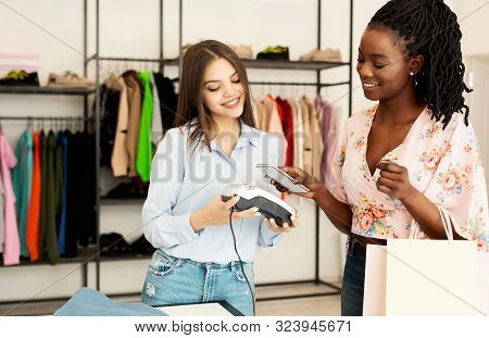 Mobile Payment Application. Afro Girl Paying Via Cellphone In Fashion Boutique Buying New Clothes. Free Space For Text stock photo