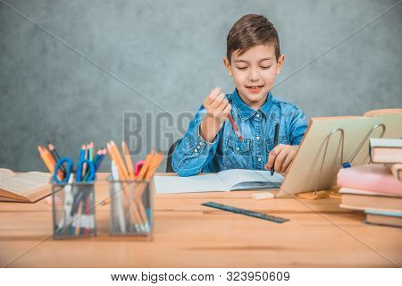Learning process. Boy in casual clothes holding two pens, red and black, thinking what to write. stock photo
