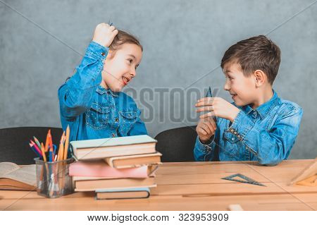 Boy and girl sitting et the table, playing around, smiling. Table full of school supplies. stock photo