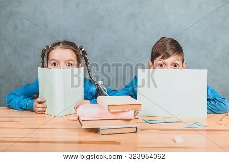 Curious little boy and girl hiding behind the sheets of papers, looking over, at the camera, conspiciuosly. stock photo