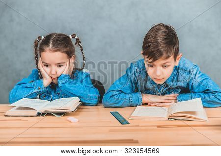 Smart boy and girl totally involved in the process of reading. stock photo