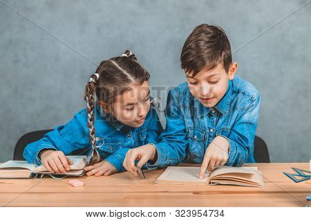 Smart boy and girl totally involved in the process of reading. Boy is pointing at something interesting in his book. stock photo