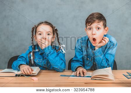 Smart boy and girl are surprised by something they have read in the books. stock photo