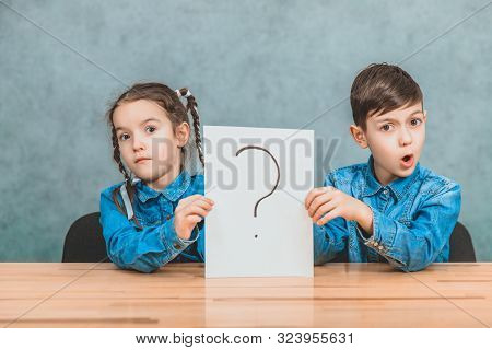 Cute schoolkids sitting at th desk, holding a sheet of paper with the exclamation mark written on it, having no idea what it means. Asking face expressions. stock photo