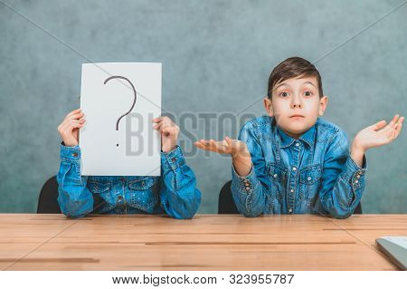 Schoolchildren sitting at the desk. Girl is hiding behind the sheet of paper with exclamation mark. Boy is throwing his hands, puzzled face expression. stock photo