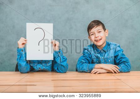 Schoolchildren sitting at the desk. Girl is hiding behind the sheet of paper with exclamation mark. Boy is smiling at the camera. stock photo