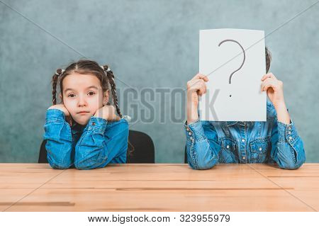 Schoolchildren sitting at the desk. Boy is hiding behind the sheet of paper with exclamation mark. Girl with funny pigtails is sitting, her elbows on the desk. stock photo