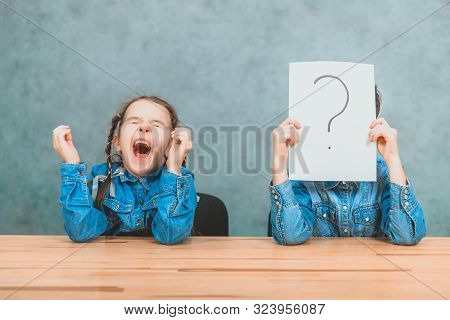 Schoolchildren sitting at the desk. Boy is hiding behind the sheet of paper with exclamation mark. Girl with funny pigtails is yawning. stock photo
