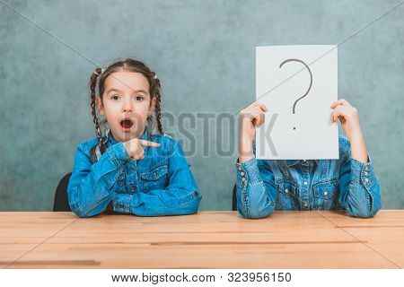Schoolchildren sitting at the desk. Boy is hiding behind the sheet of paper with exclamation mark. Girl with funny pigtails is pointing at him with her finger, looking astounded. stock photo