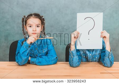 Schoolchildren sitting at the desk. Boy is hiding behind the sheet of paper with exclamation mark. Girl with funny pigtails is pointing at him with pencil. stock photo