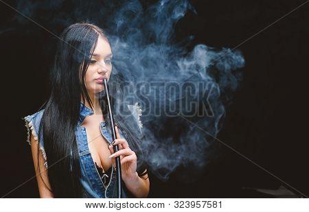 hookah bar. Electronic cigarette. Bad habit. Woman vapor. unhealthy addiction. Tabacco drug. exhale smoke on black background. stock photo