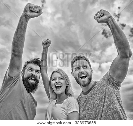 Woman and men look confident successful sky background. Behaviors of cohesive team. Celebrate success. Yes we can. Ways to build ohesive team. Threesome stand happy confidently with raised fists stock photo