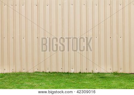 a metal sheet wall on a green grass stock photo