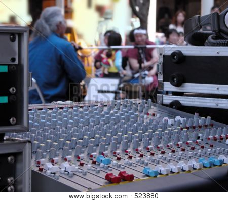 interesting perspective of a street music performance. selective focus on the sound master command desk, the artist and the audience are out of focus. stock photo