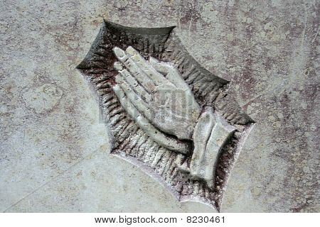 The praying hands chiseled in a gravestone stock photo
