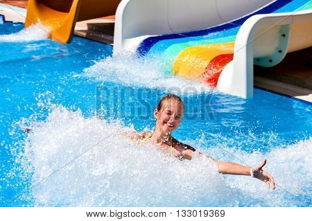 Child on water slide at aquapark and hands to side. There are two water slides with flowing water in aqua park. Summer swimming holiday. Outdoor. stock photo