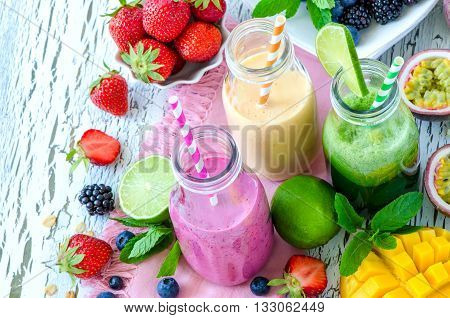 Berry and fruit smoothie in bottles healthy summer detox yogurt drink diet or vegan food concept fresh vitamins mango lime passtion fruits
