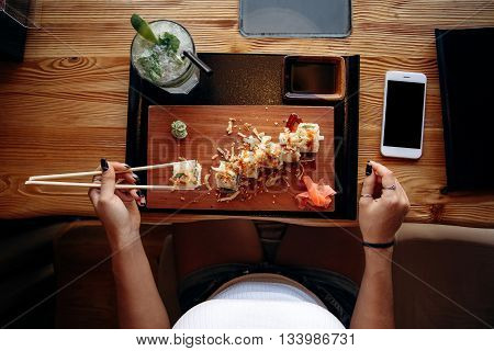 Girl takes sushi in the japanese restaurant. View from above.