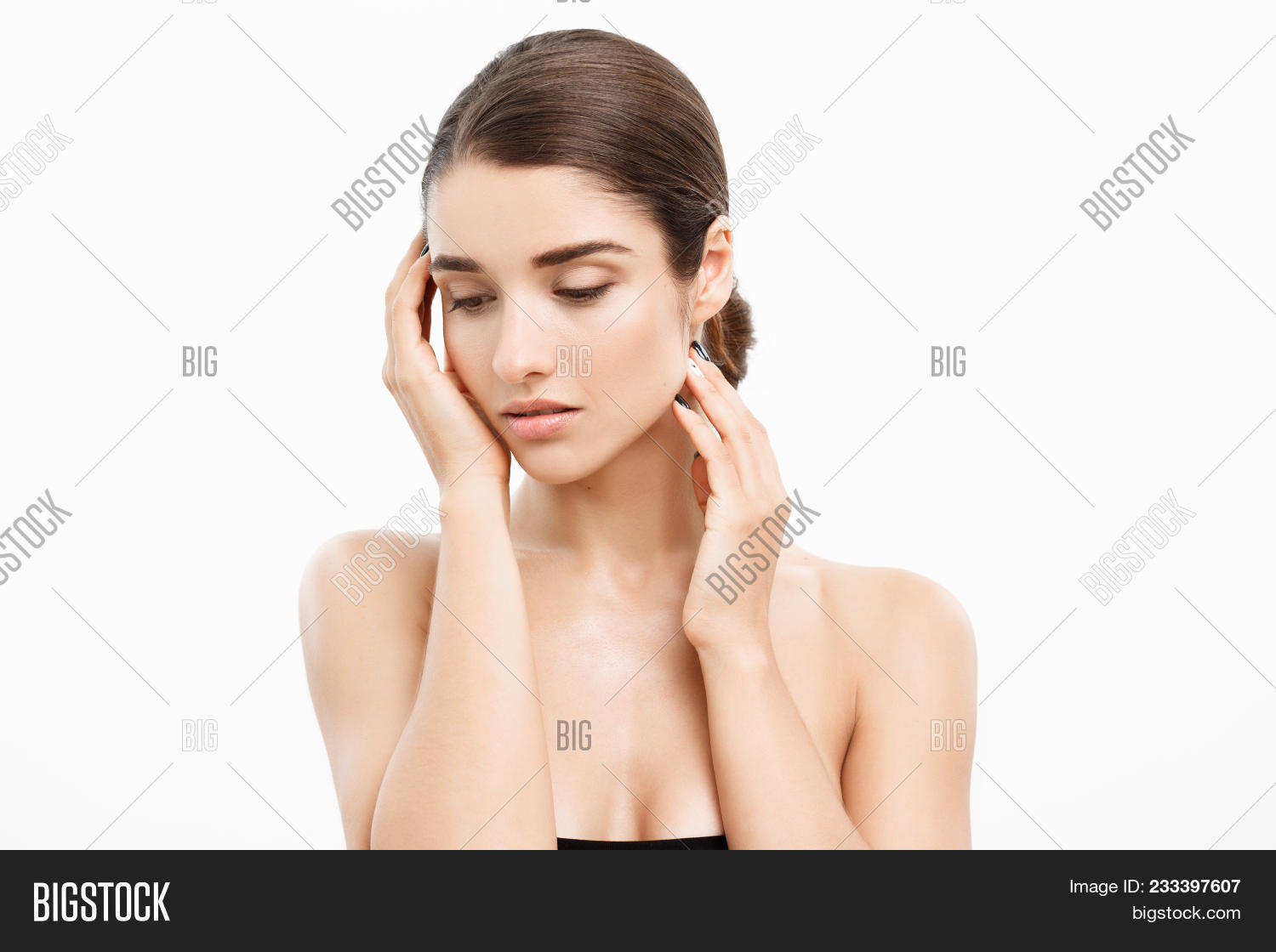 Beauty Skin Care Concept - Beautiful Caucasian Woman Face Portrait. Beautiful beauty young female model girl touching her face skin cheeks hands fingers. Fashion Beauty Model isolated on white.