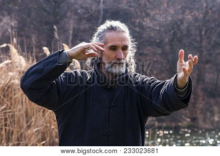 mature man practicing Tai Chi discipline outdoors in a lake park on a winter day stock photo