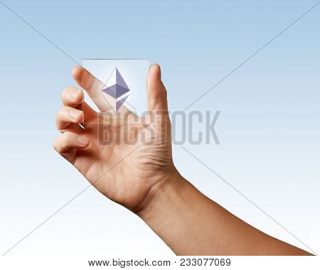Icon of etereum on a digital screen man holds on a blue background stock photo