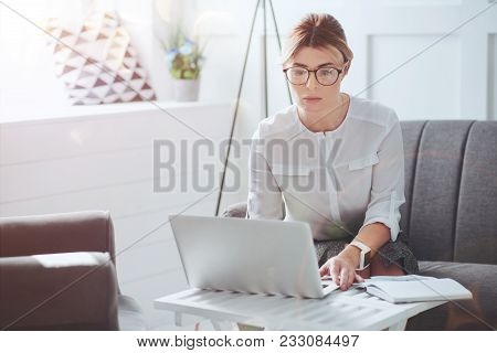 Professional businesswoman. Attractive nice hard working businesswoman sitting in front of the laptop and looking at its screen while focusing on her work stock photo