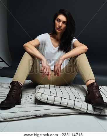 brunette girl sitting in Studio on mattress stock photo