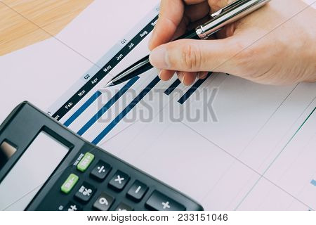 Finance, business budget planning or analysis concept, hand holding pen reviewing quarter and monthly chart and graph information report with calculator on office desk. stock photo