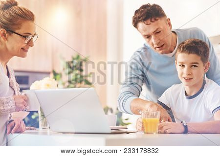 Look at this. Attentive man standing behind his son and pointing at necessary task while looking downwards stock photo