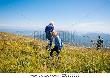 Happy young family gathers berries in the mountains stock photo