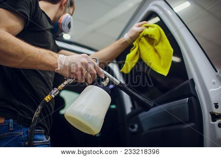 Handsome man cleaning car with hot steam male stock photo
