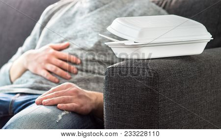 Man having stomach pain or digestion problem. Couch potato, lazy or unemployed person taking nap. Feeling bad after eating too much fast junk food. Guy with unhealthy diet or hangover. stock photo