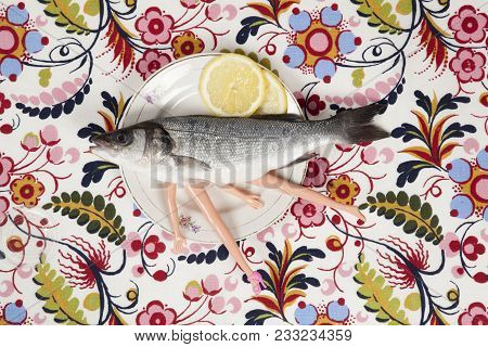 A bass fish with arms and legs of a doll inside on a flower plate. Cannibalism and anthropomorphism on a floral fabric patterned background. Quirky minimal color still life photography. stock photo