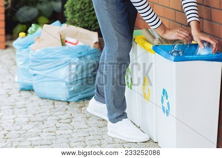 Housewife throwing paper into yellow bin. Segregation of garbage in the household concept stock photo