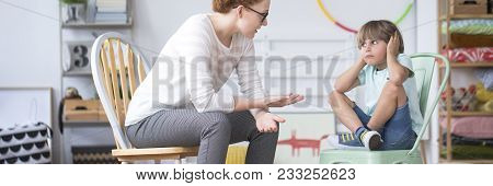 Disobedient kid sitting on a mint chair and a coach teaching him stock photo