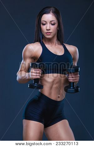 Brutal athletic sexy woman pumping up muscules with dumbbells. The concept of exercise sports, advertising a gym stock photo