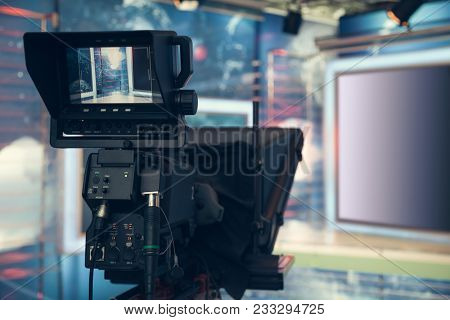 Television studio with camera and lights - recording TV NEWS. Shallow depth of field - focus on camera. stock photo