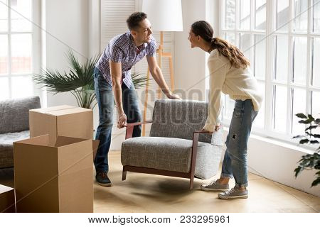 Smiling Couple Carrying Modern Chair Together Placing Furniture Moving Into New Home, Young Family D