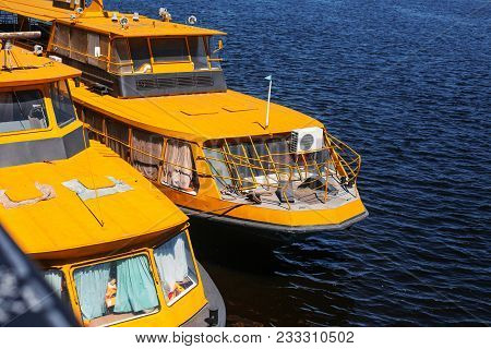 yellow boats in docks of city capital in sunny summer day. ship in blue waters on background of city buildings, pier with cargo and passengers marinas stock photo