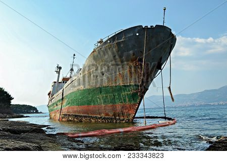 An old ruined ship sits rusting on the shore. stock photo