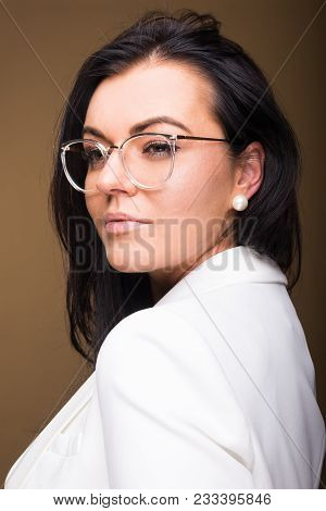 Beautiful brunette business woman holding her hair wearing glasses on brown background with copypsace advertising area stock photo
