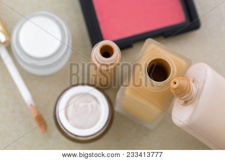 Cosmetic makeup, liquid foundation in glass bottle, plastic tube, creamy concealer, blush in pink coral shade, skin care product, selective focus stock photo