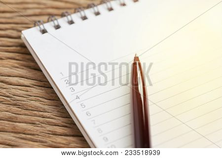 organize or writing projects, personal to do lists or work, tasks priority concept, closed up of black pen on list of numbers with lines on white clean paper notepad on wooden table. stock photo